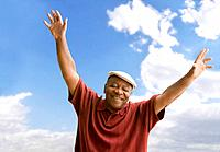 Senior African man with arms raised