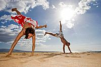 Hispanic couple doing cartwheels on beach