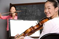 Asian girl holding violin in music class