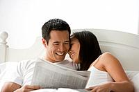 Asian couple reading newspaper in bed