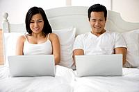 Asian couple typing on laptops in bed