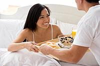 Asian man bringing girlfriend breakfast in bed