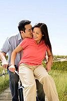 Asian couple riding on bicycle
