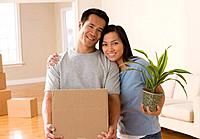 Asian couple holding moving box and plant
