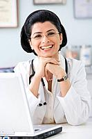 Middle Eastern female doctor next to laptop