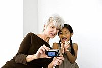 Senior woman photographing self and granddaughter with digital camera, both laughing