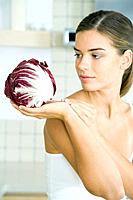 Woman looking at and holding a head of radicchio lettuce