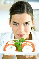 Young woman holding up a plate of tomato mozzarella salad, smiling at camera
