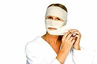 Woman removing bandages from face, looking at camera