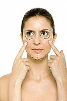 Woman with plastic surgery markings on face, touching cheeks, looking away