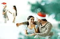 Couple sitting on sofa, drinking champagne, man wearing Santa hat