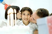 Family behind birthday cake with lit candles, parents kissing boy on cheeks