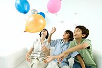 Mother and two sons playing with balloons, looking up