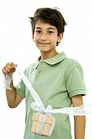 Boy holding present up by a ribbon, smiling at camera, portrait