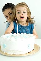 Girl blowing out candle on birthday cake, sister peeking at camera from behind