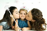Girl dressed as princess, holding wand, mother and sister kissing her cheeks