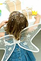 Little girl wearing wings, confetti in her hair, rear view