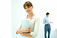 Female professional holding documents, smiling at camera