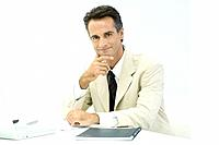 Business executive sitting at desk, smiling at camera, portrait