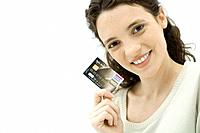 Woman holding credit card, smiling at camera