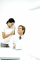 Man sitting at desk, smiling over his shoulder at female colleague standing behind him