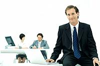 Businessman sitting with laptop, smiling at camera, colleagues in background