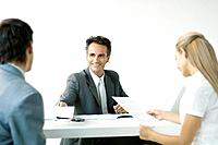 Businessman discussing contract with couple, smiling
