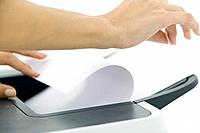 Hands arranging paper in printer, cropped