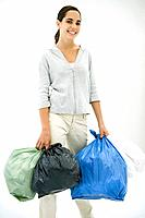 Teen girl carrying several garbage bags, smiling at camera