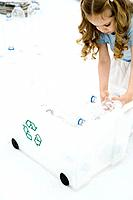 Little girl bending over, placing plastic bottles in recycling bin