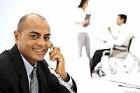 Businessman using phone, smiling at camera, colleagues in background