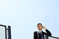 Businessman using cell phone outdoors, smiling at camera, low angle view