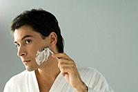 Man shaving, wearing bathrobe, head tilted