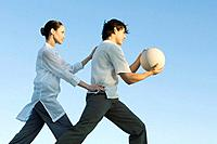 Man holding fitness ball, woman positioning man