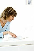 Woman using laptop, coffee cup and saucer nearby