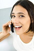 Woman using cell phone, looking at camera, laughing