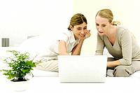 Two women looking at laptop computer together, smiling