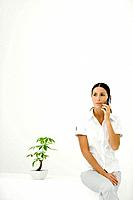 Woman sitting beside potted plant, using cell phone