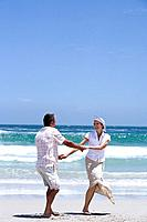 Mature couple holding hands on beach, smiling at each other