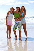 Three teenage girls 14-16 arm in arm on beach, smiling, portrait
