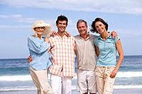 Couple with parents arm in arm on beach, smiling, portrait