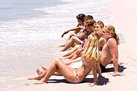 Group of teenagers 15-17 sitting in line on beach, side view