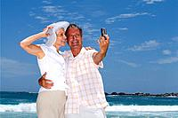 Mature couple taking photograph of themselves on beach with mobile phone, smiling, low angle view