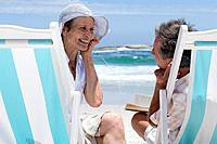 Mature couple on deck chairs on beach sharing earphones, smiling at each other