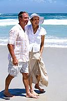 Mature couple walking on beach, smiling