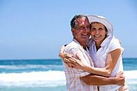 Mature couple embracing on beach, smiling, portrait