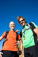Young couple hiking, smiling, portrait, low angle view