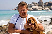 Man embracing dog on beach, smiling, portrait
