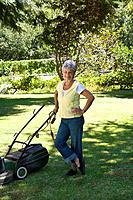 Senior woman with lawnmower, hand on hip, smiling, portrait