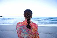 Woman on beach, looking out to sea, rear view